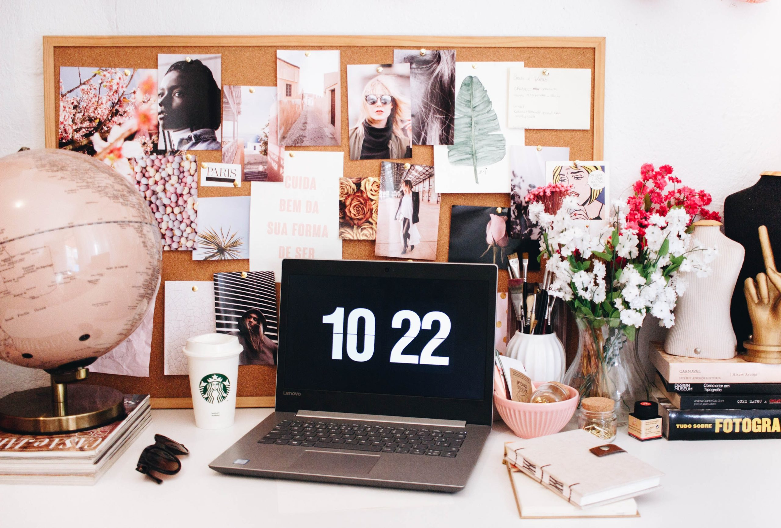 a cut desk with a laptop, globe, flowers and more on it