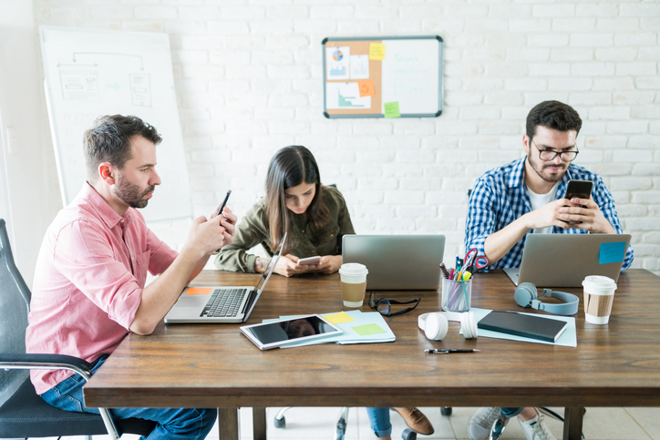 Distracted Colleagues Using Cellphones At Workplace
