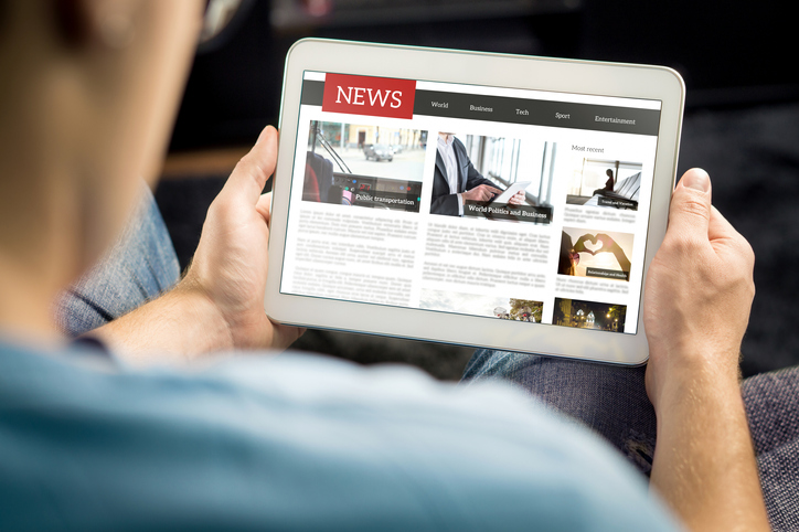 Online news article on tablet screen. Electronic newspaper or magazine. Latest daily press and media. Mockup of digital portal and website. Happy person using web service in the morning.