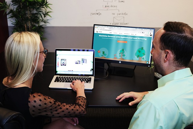 A woman on her laptop showing a male coworker how to create video infographics. A second screen is in the background.