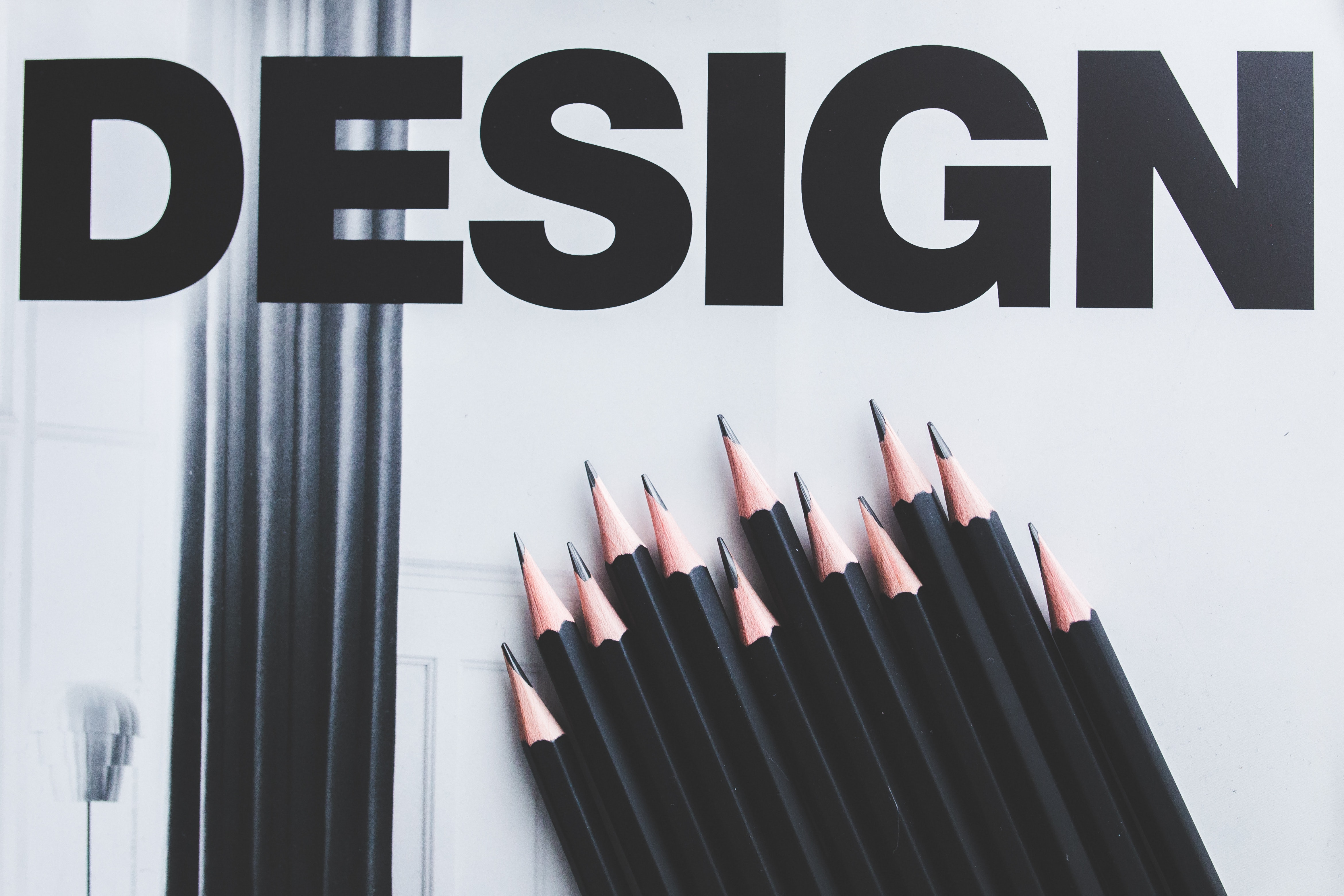 "Twelve black pencils on a white background under the word ""Design"""
