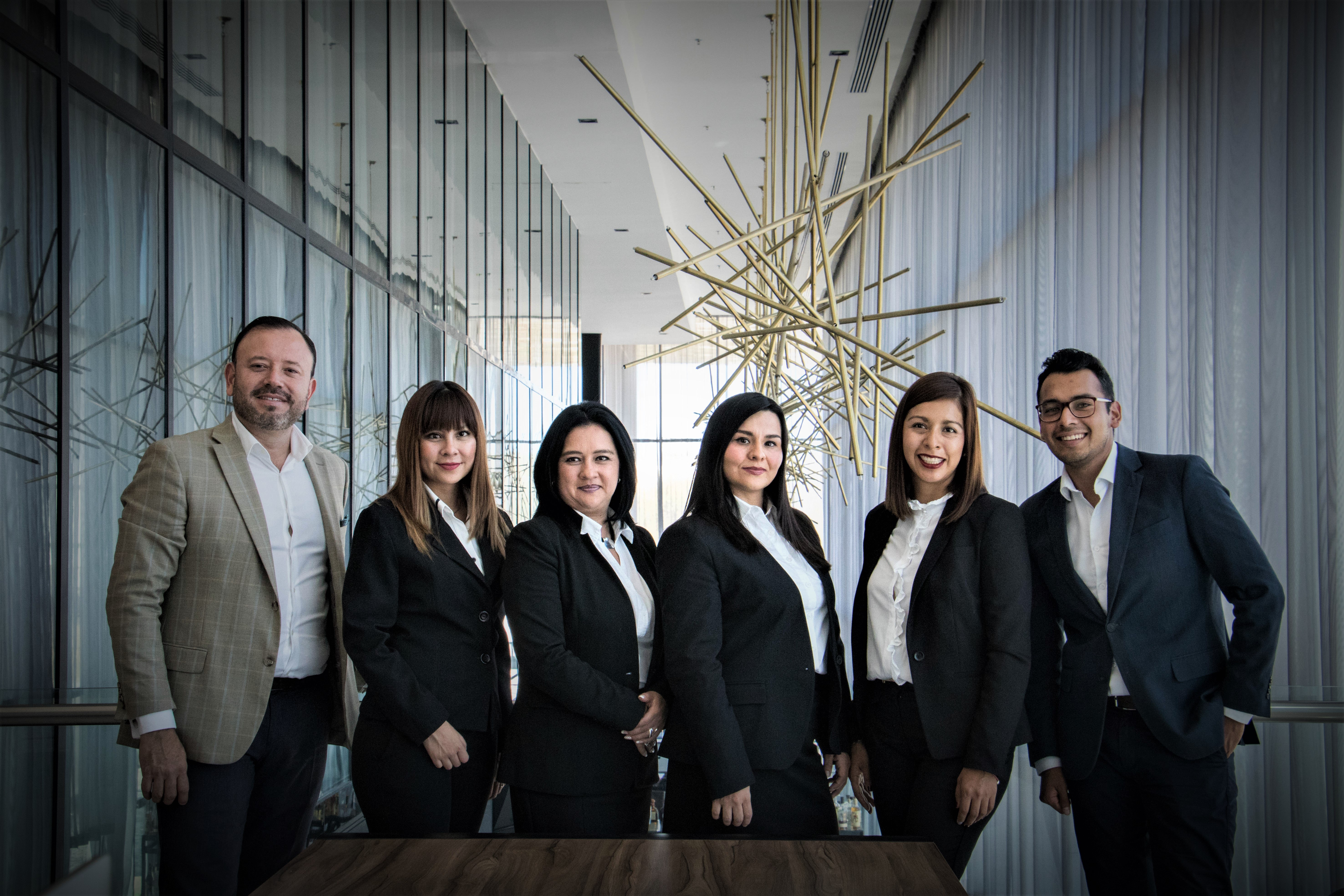 A team of six marketing professionals in a business lobby.