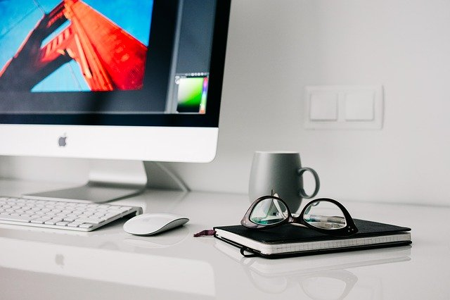 An Apple computer with a design program open, a black notebook, glasses, and a coffee cup on the desk.