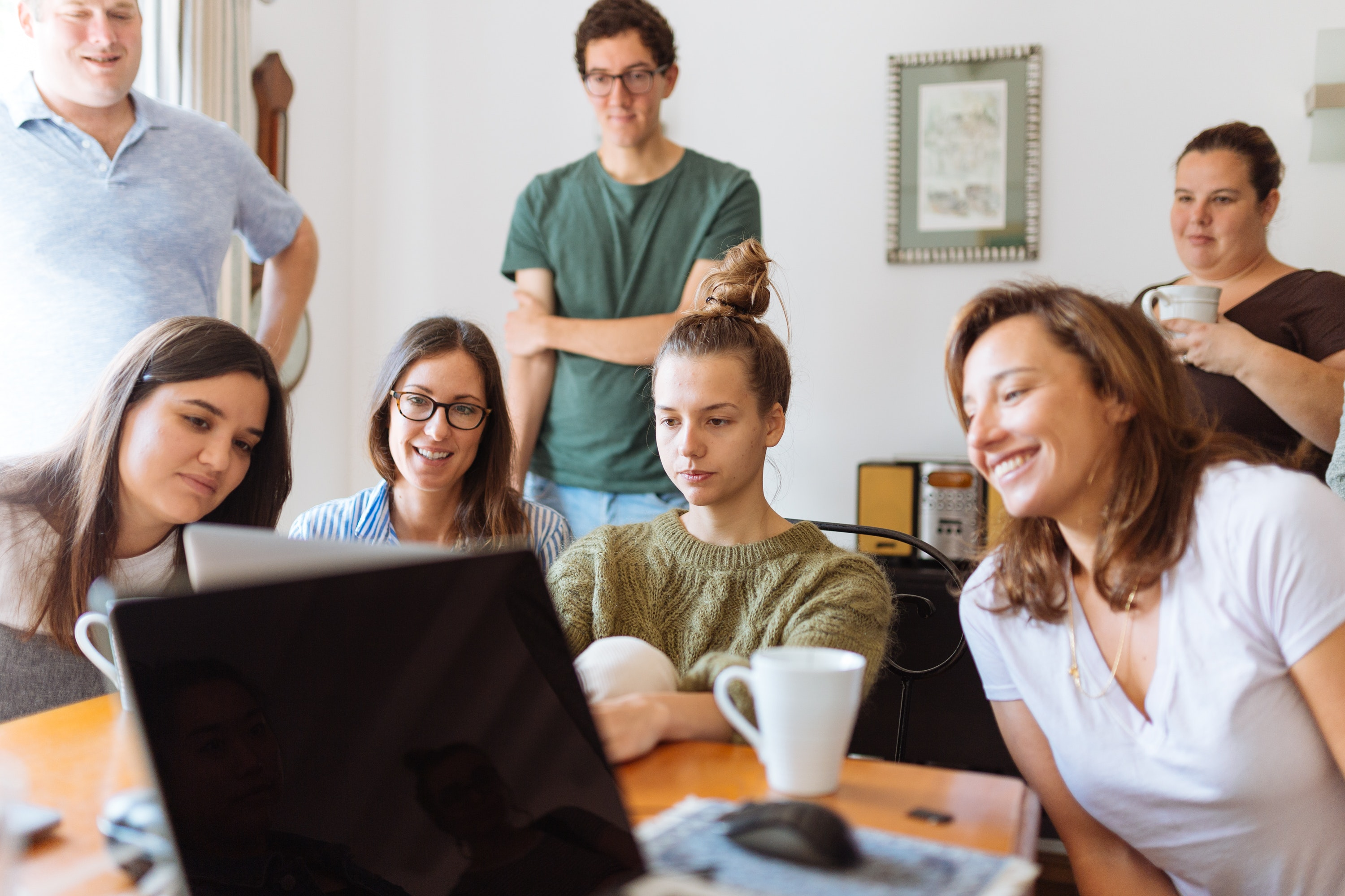 A marketing team of seven people huddled around a table looking at a laptop.