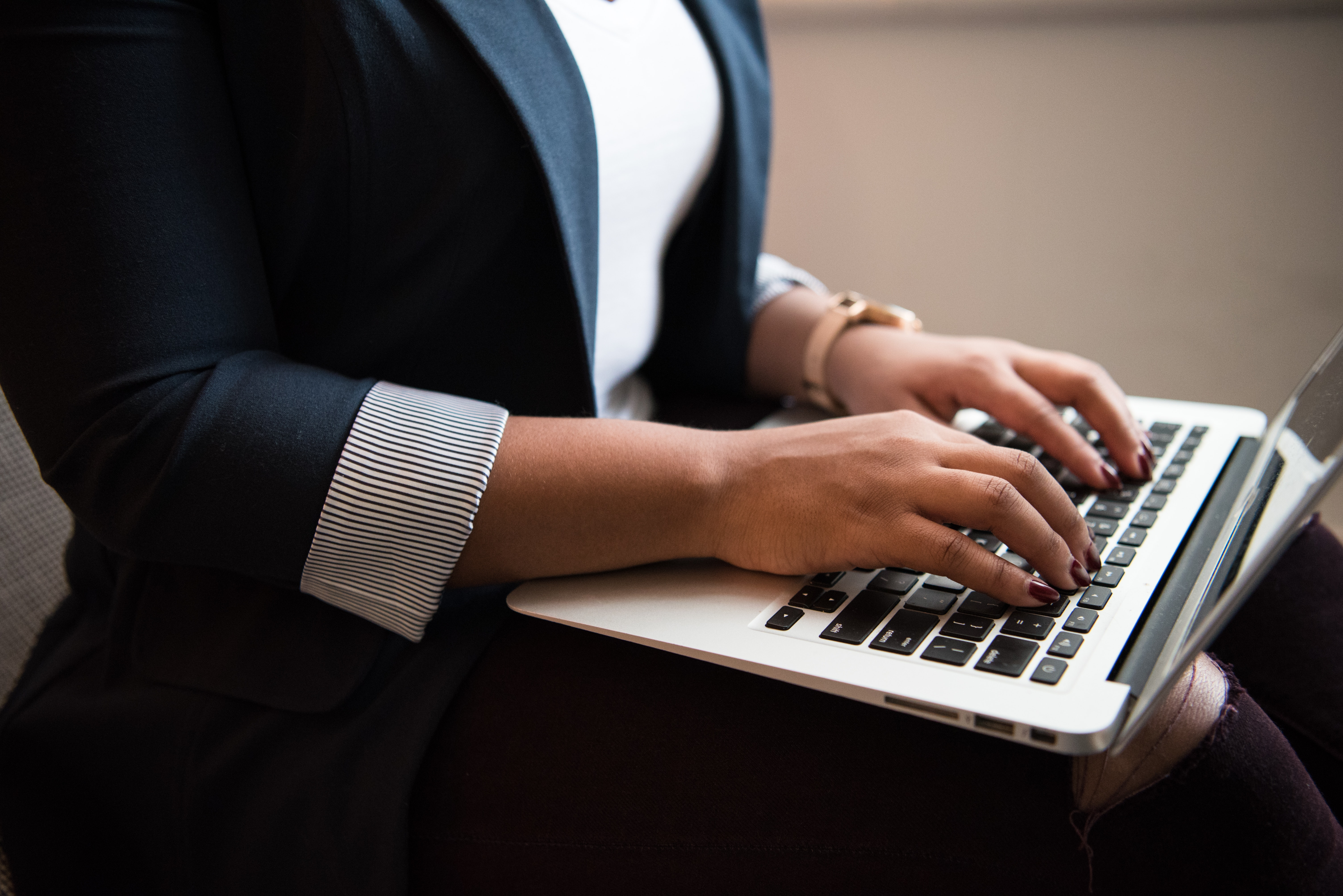 A powerful business woman wearing professional clothing typing on her laptop.