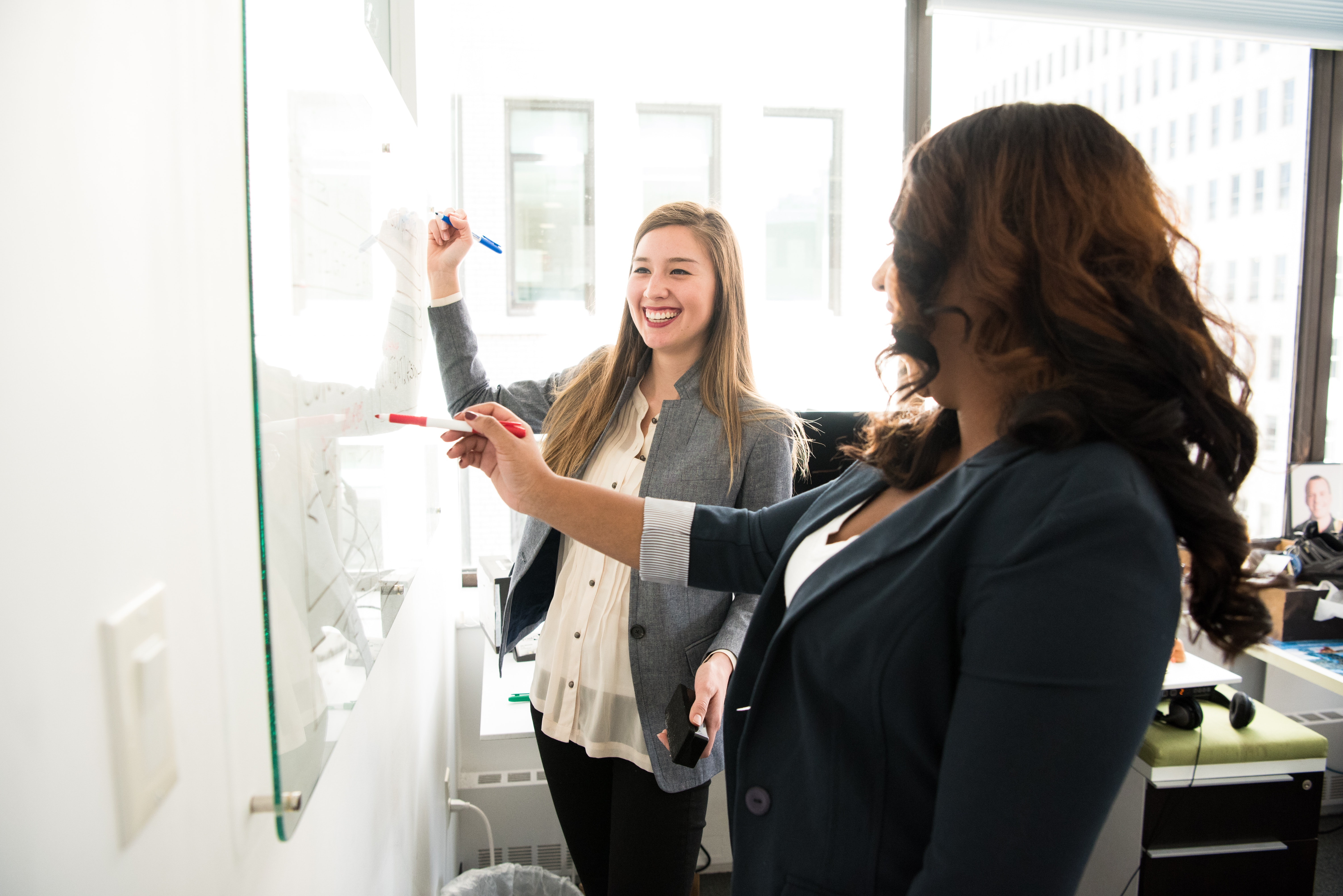 Two professional women writing on a white board to layout their timeline infographic.