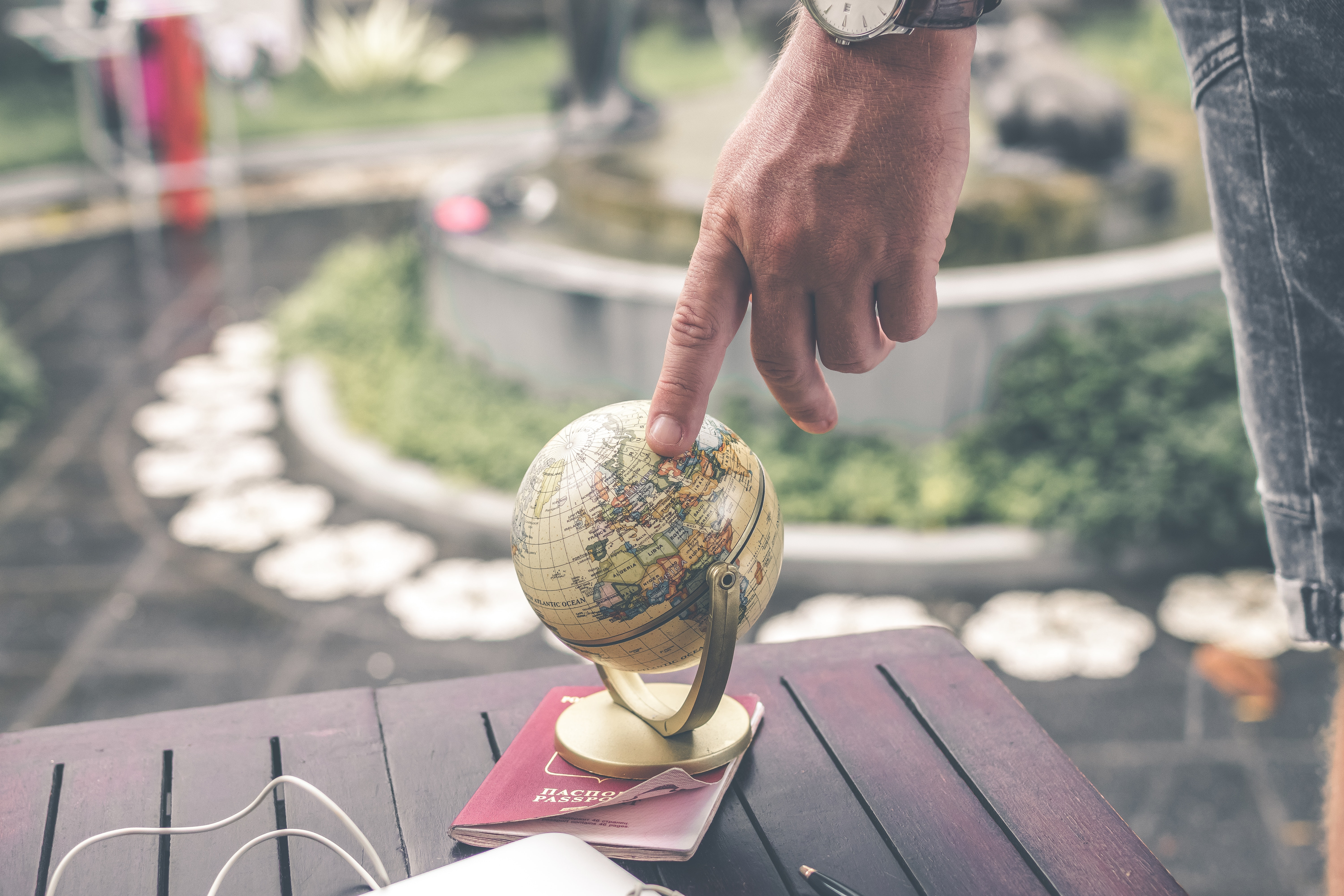A man touching a miniature globe on top of a side table with a passport under the globe.