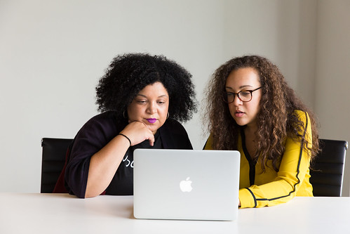 Two women reviewing how to market white papers