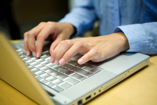 person typing on their laptop's keyboard