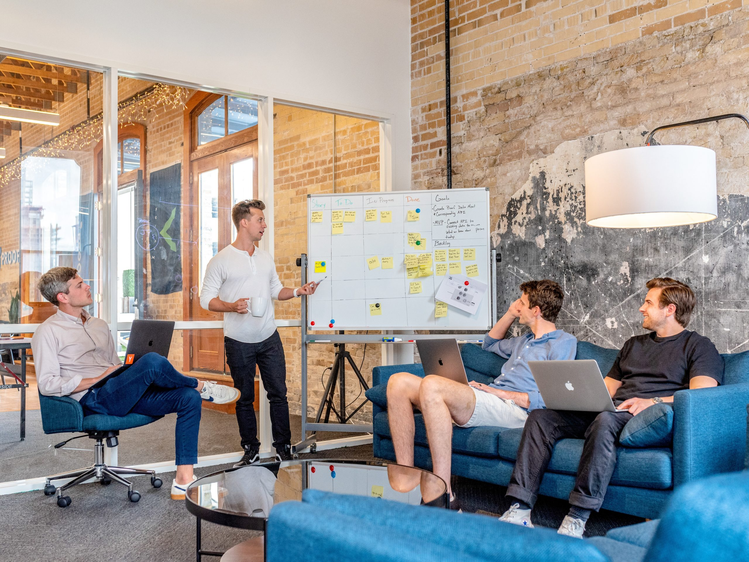 four coworkers in a meeting with a board filled with ideas