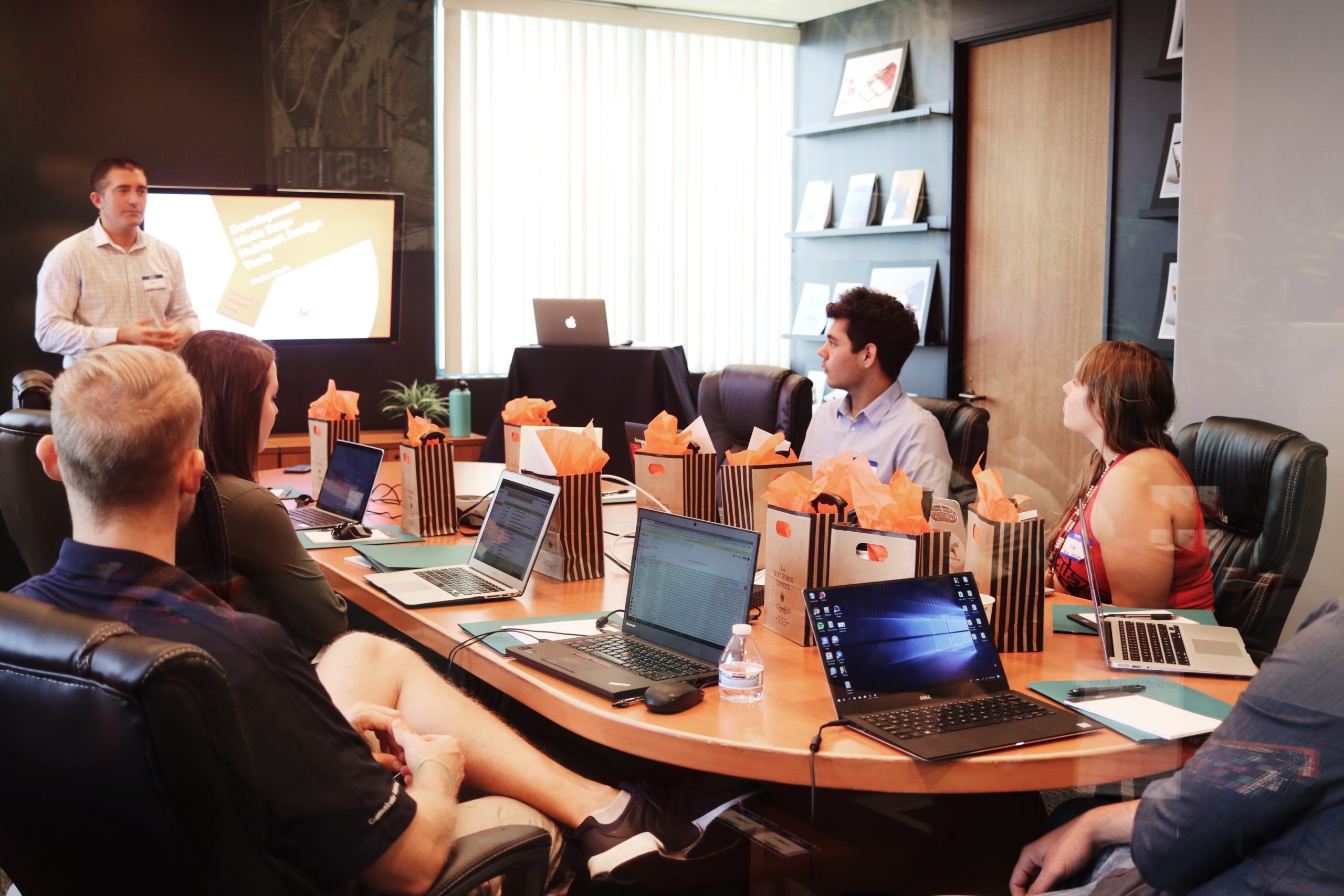 a man leading a meeting in front of four employees with gift bags and laptops on the desk