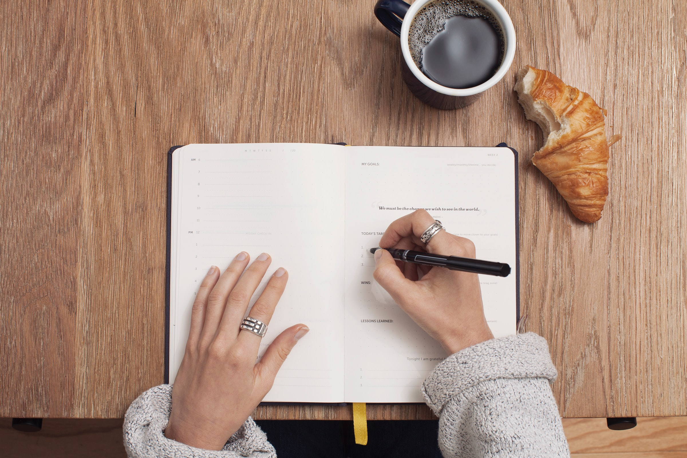 person writing in their calendar with a snack and coffee also on the desk