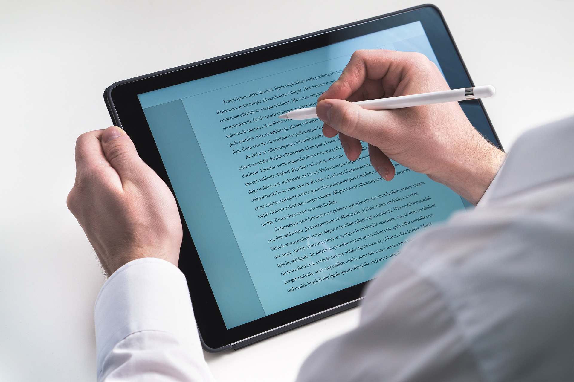 Man using tablet to write over what is already typed out on the screen