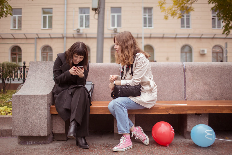 Women sitting at a bench with a ball by their feet and a phone in ones hand