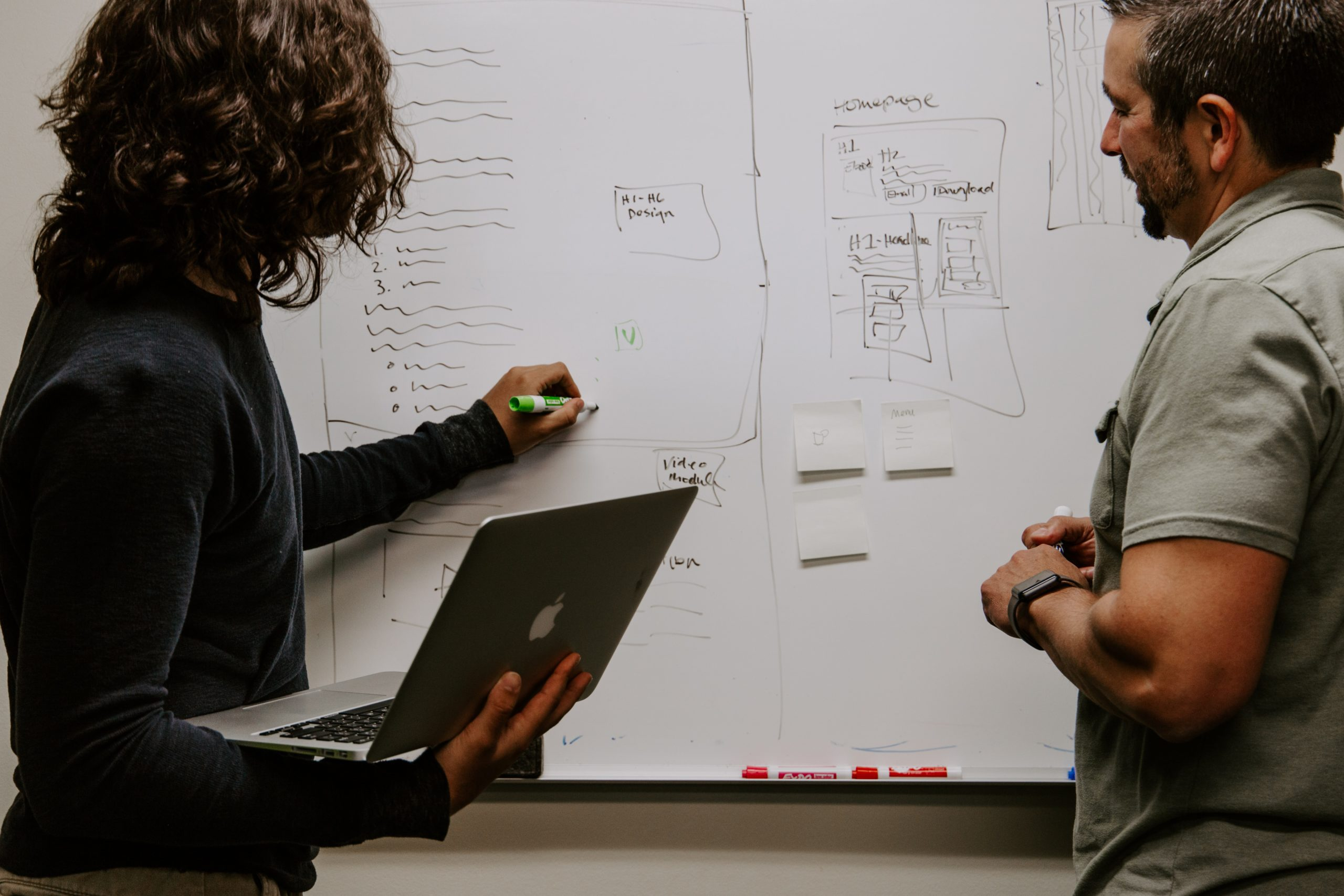 two people creating a marketing strategy on a whiteboard with charts