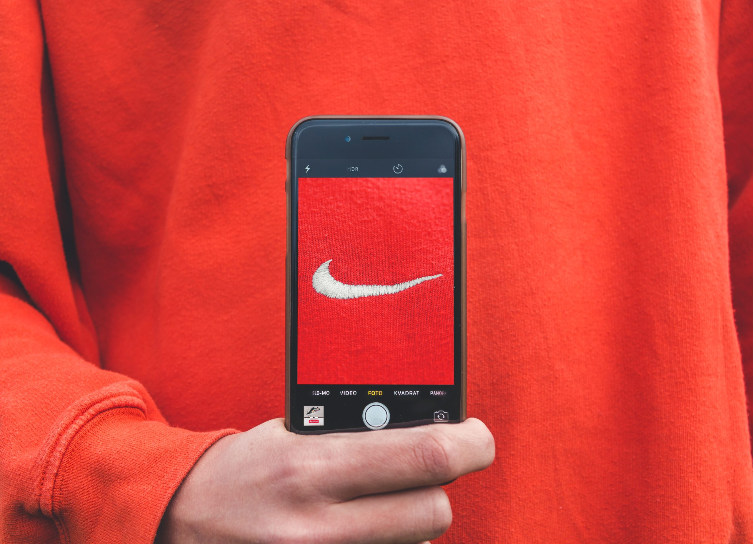 nike symbol on a sweatshirt with a phone taking a photo of the symbol
