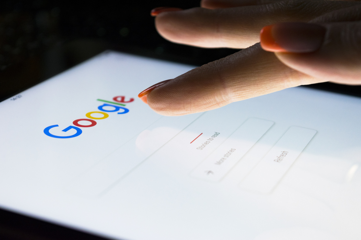 A woman's hand is touching screen on tablet computer iPad Pro at night for searching on Google search engine. Google is the most popular Internet search engine in the world.