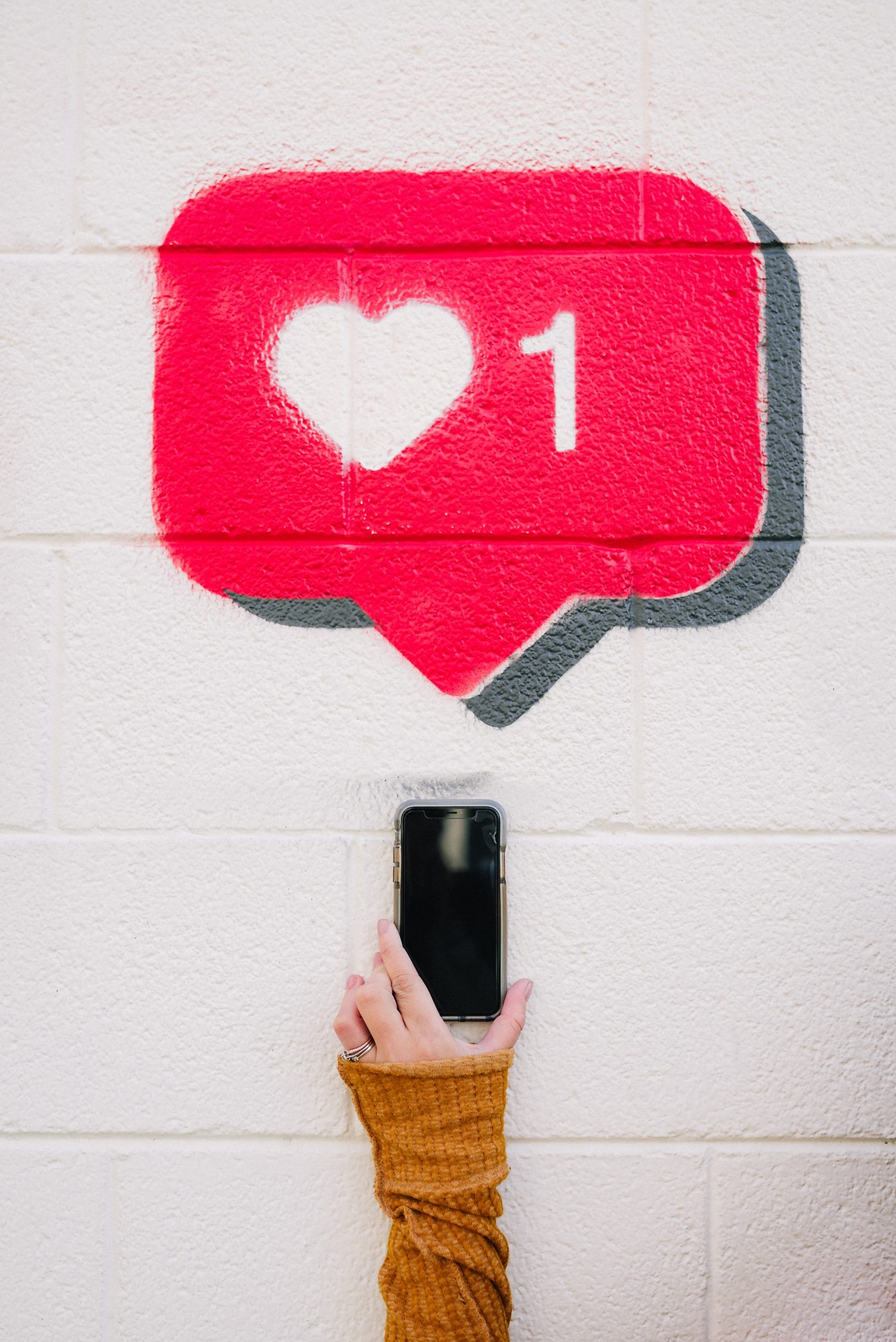social media notification bubble drawn in pink chalk on a white brick background, has a heart with a number one next to it in the bubble, a hand holding a black cell phone is below