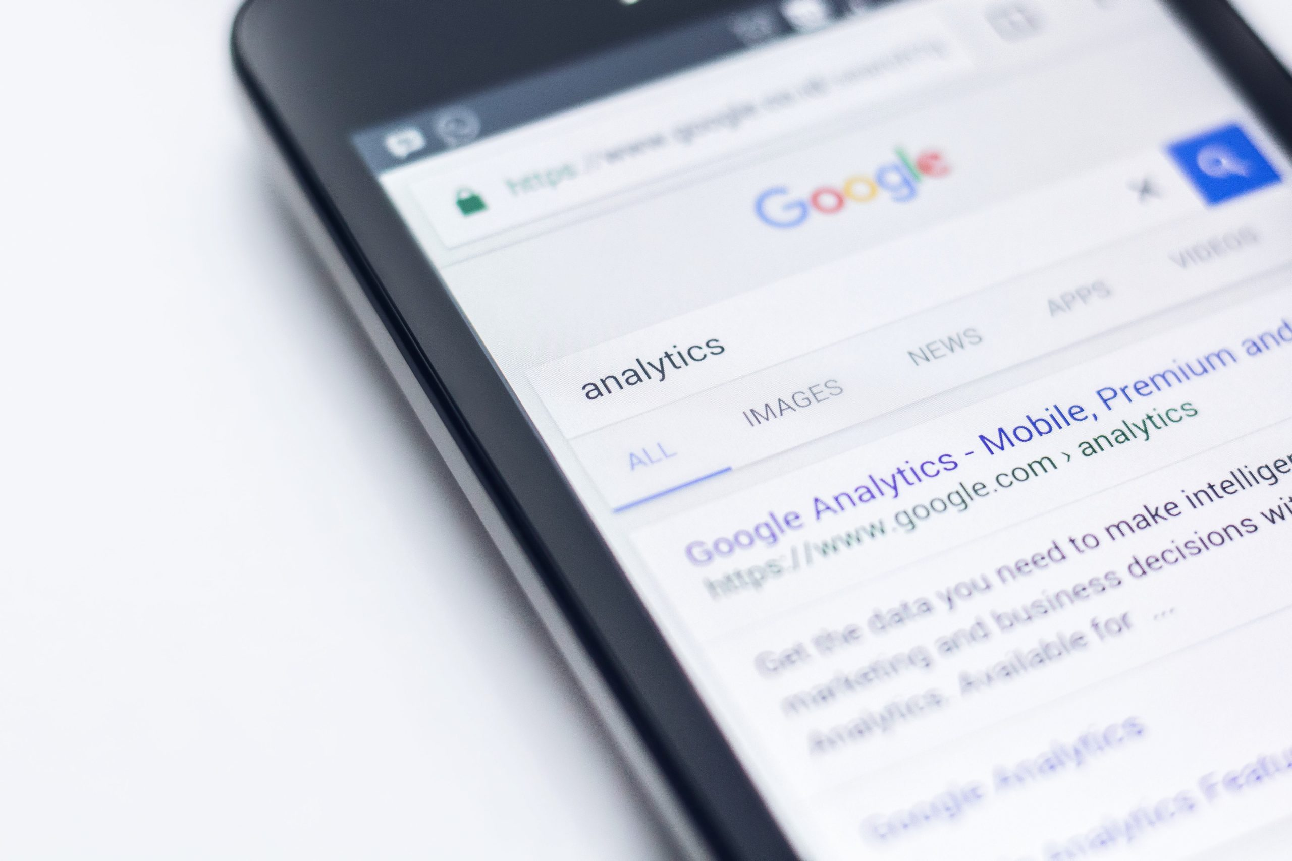 black iphone on white background showing google search for the word analytics