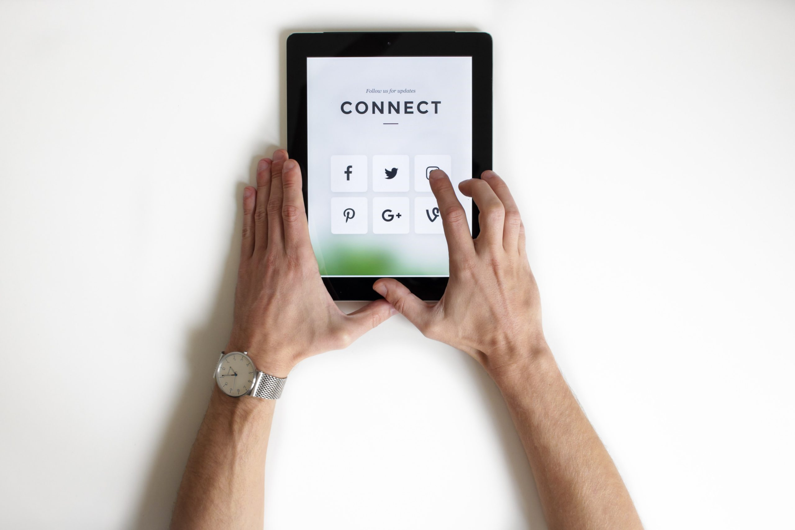 Tablet on white background, hands clicking social media icons on the screen