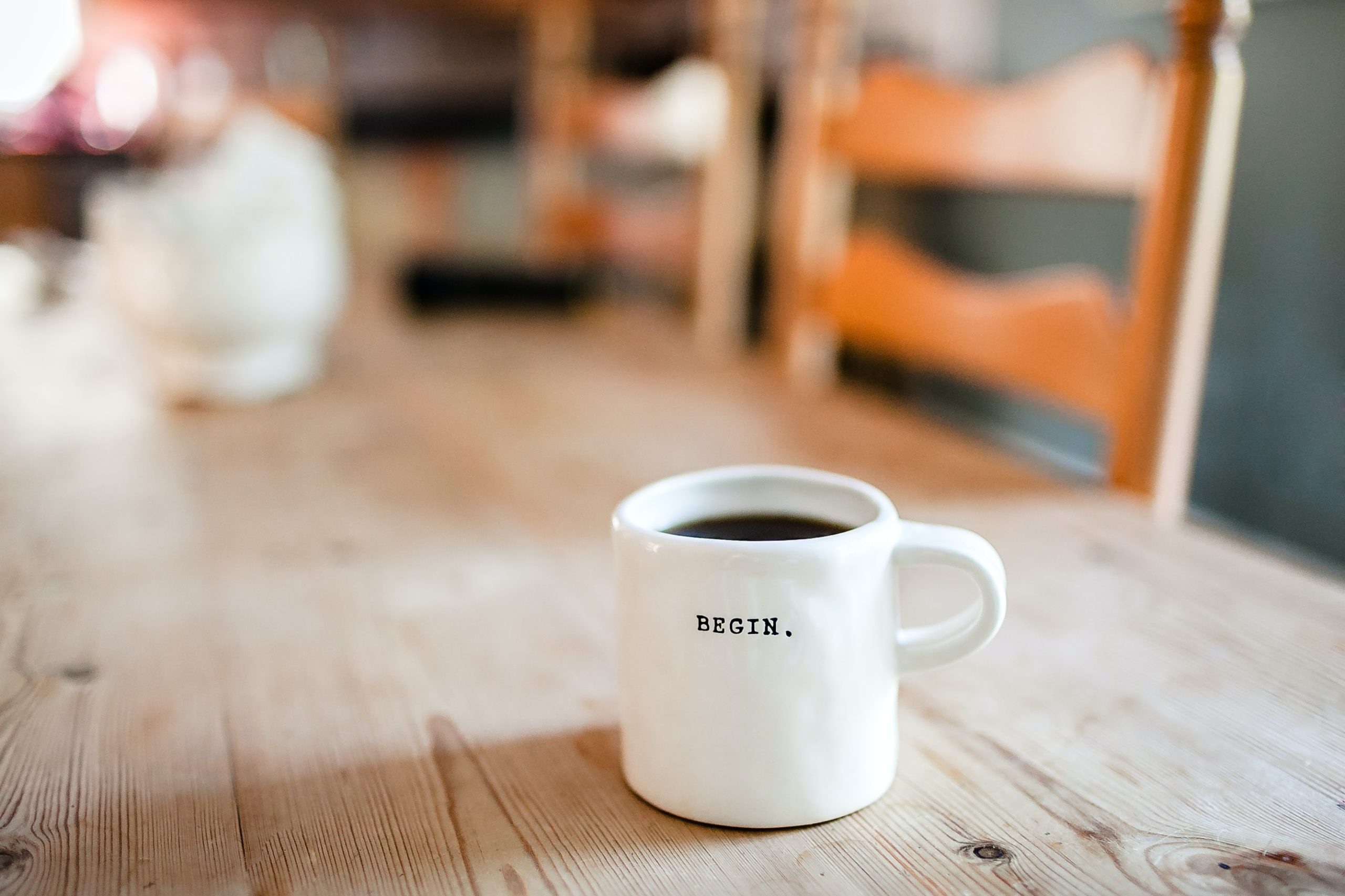 white coffee mug on a wooden table with the word begin on it in typeface