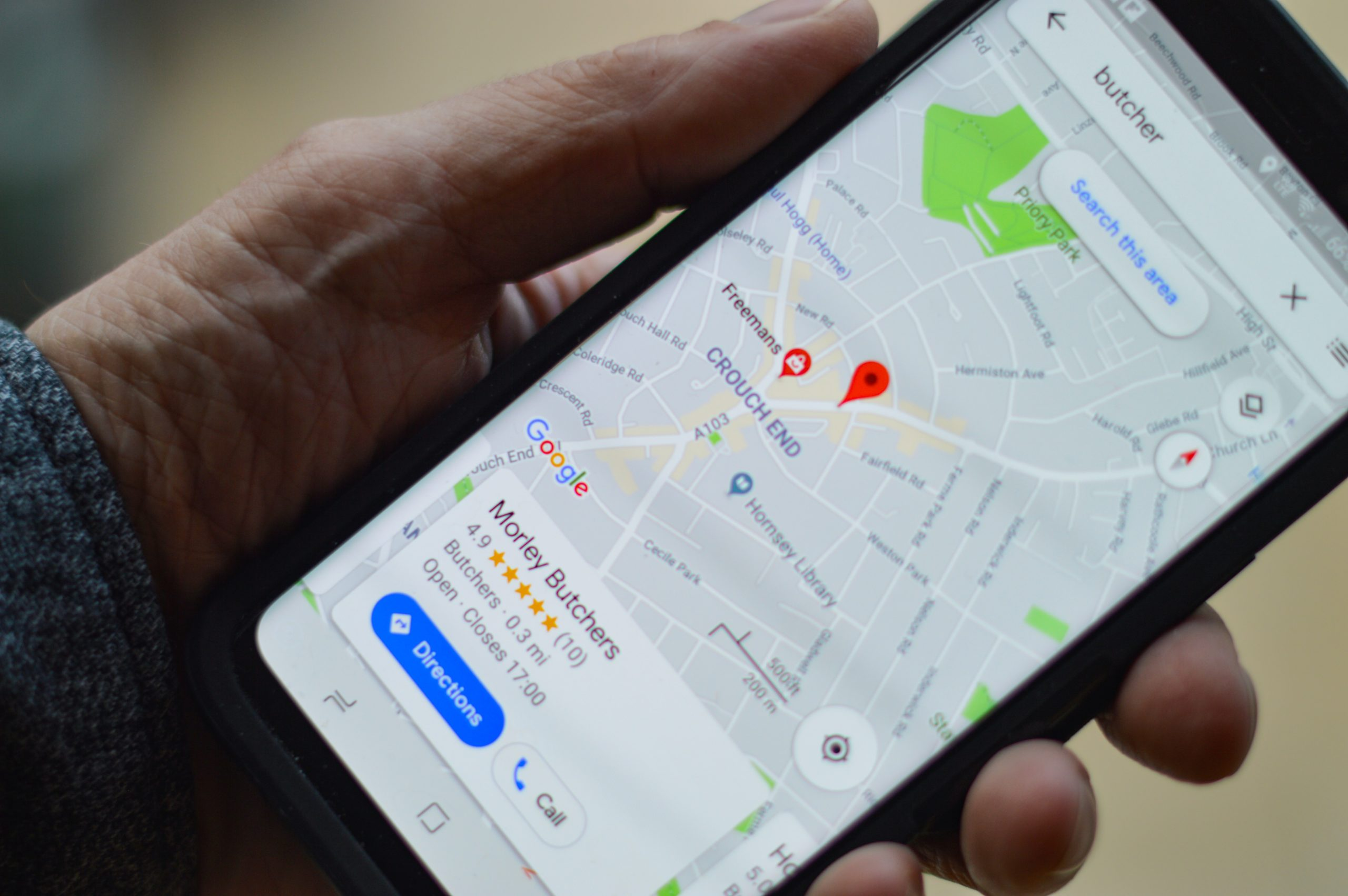 iphone in person's hand with Google maps onscreen