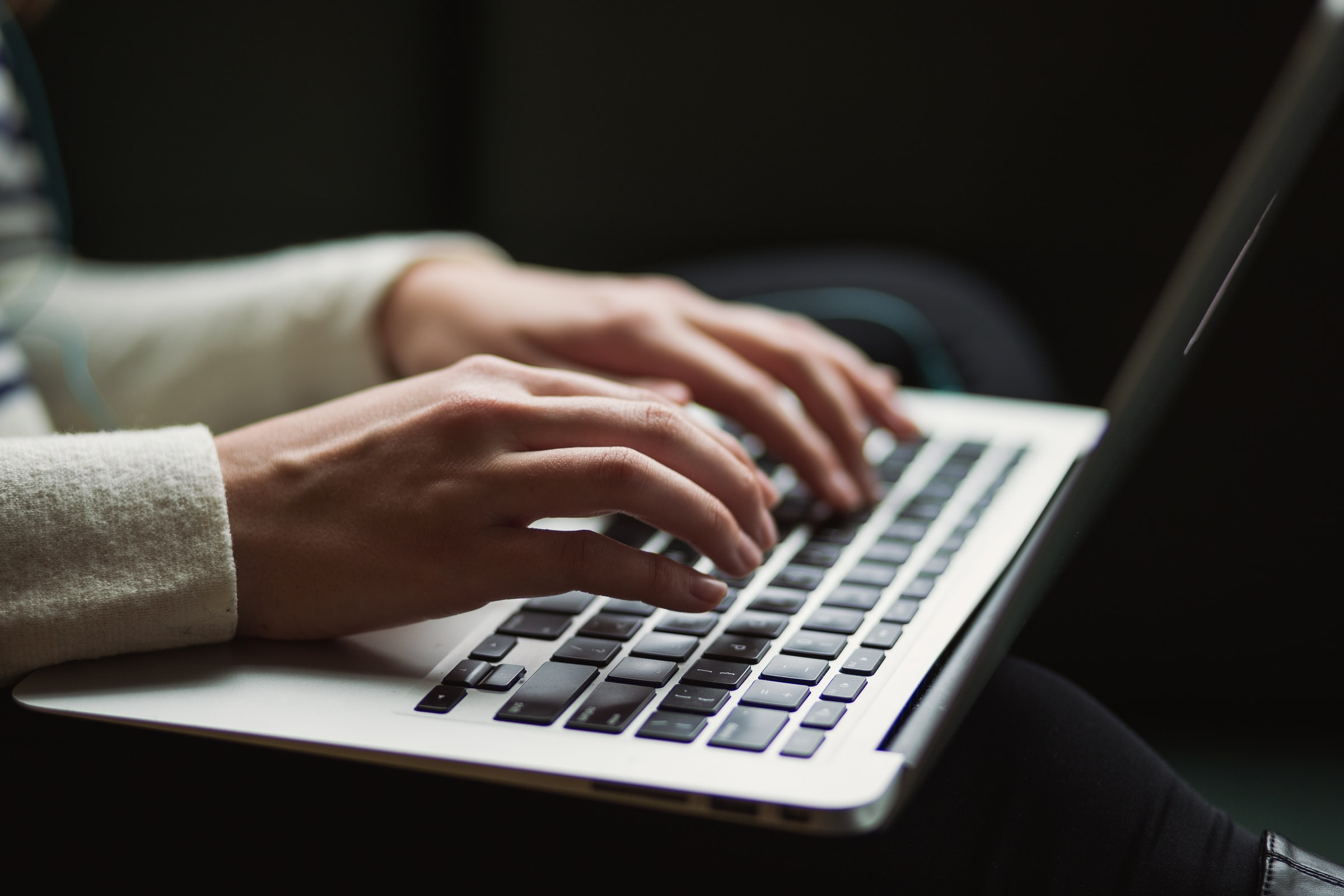 laptop sitting on a person's lap with hands over the keyboard