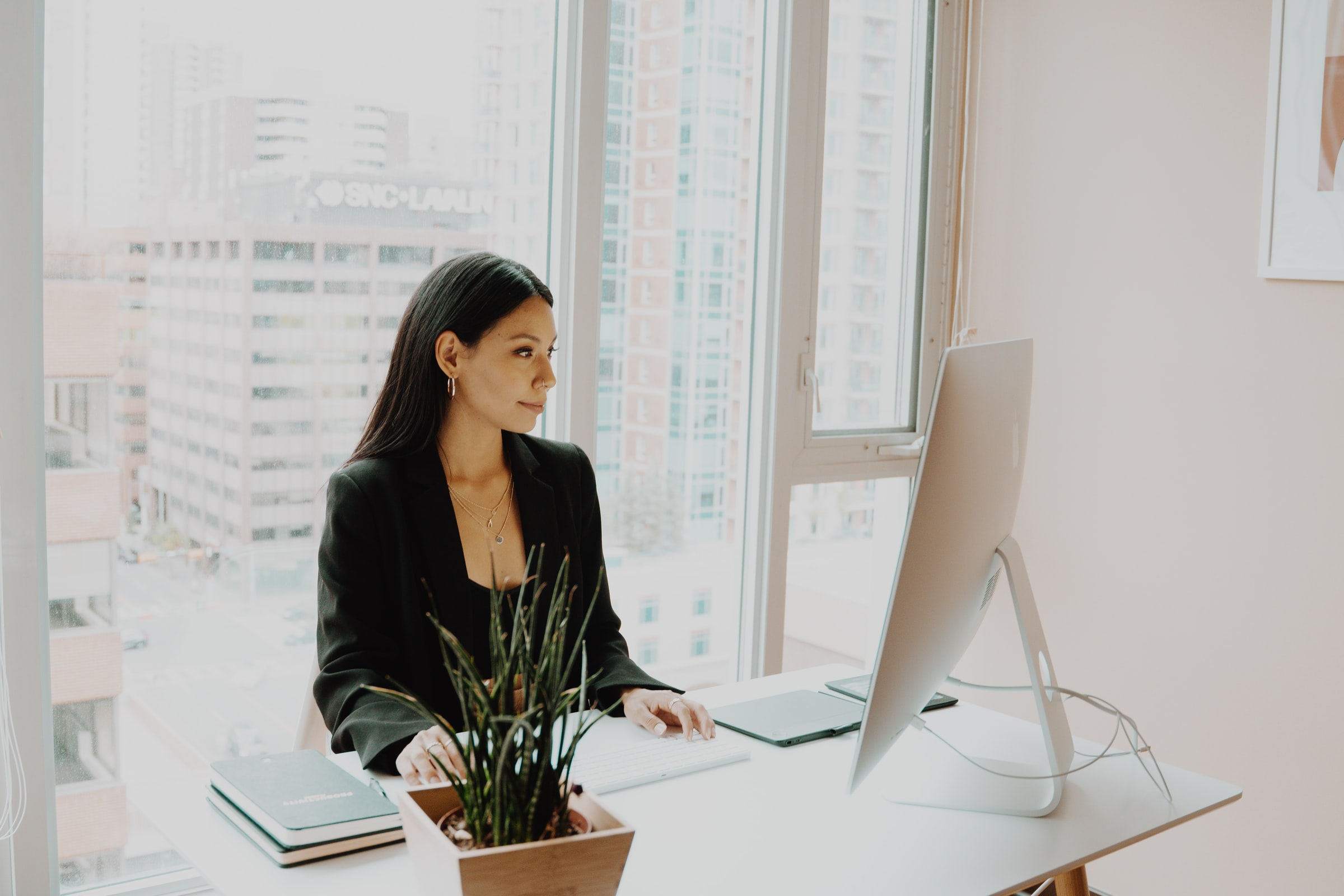 woman in black long sleeve blazer sitting at a computer in an all white office with a window behind her to show she's in a skyscraper
