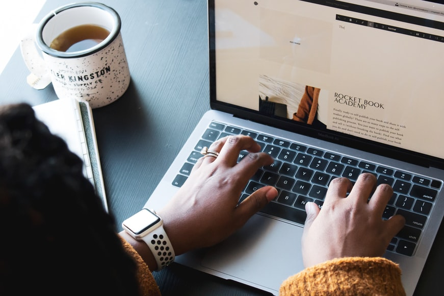 laptop on black table with coffee mug to the left, woman in yellow sweater and smartwatch had hands on the keyboard